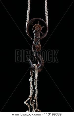Big metal hook hanging on rope isolated on black background.