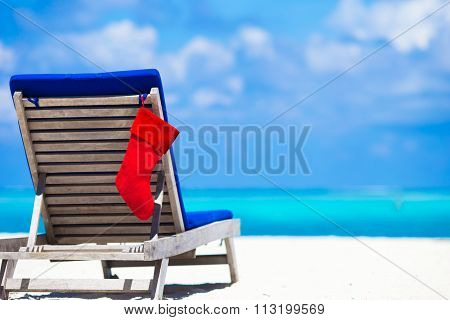 Red Christmas stocking on chair longue at tropical white beach
