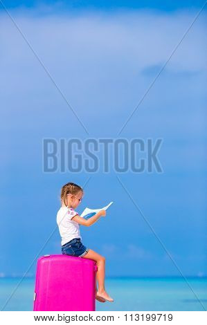 Little adorable girl with luggage and map of island during beach vacation