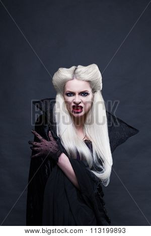 Beautiful blonde girl vampire standing