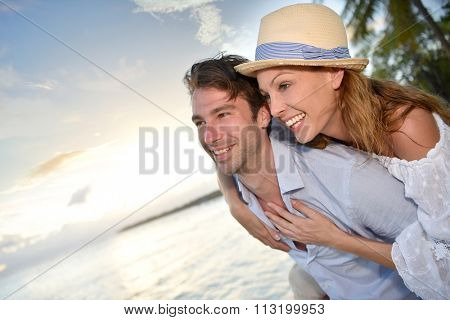 In love man giving piggyback ride to woman at the beach