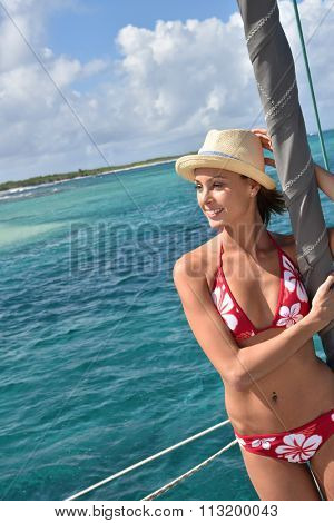 Beautiful woman standing by catamaran mast