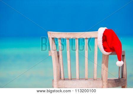 Red santa hat on chair longue at tropical white beach