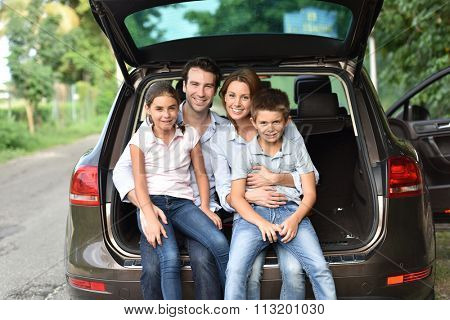 Family sitting in car trunk, ready for vacation