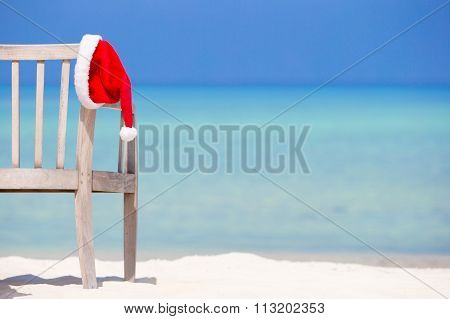 Christmas concept. Red santa hat at tropical white beach.