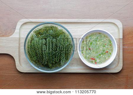 Seaweed Salad On A Wooden Floor With Seafood Sauce. Marine Algae, Sea Grapes Healthy Diet.