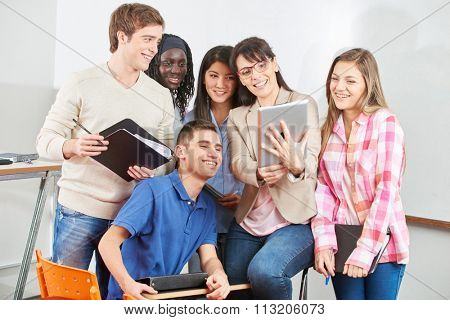 Teacher and students smiling with their tablet in class