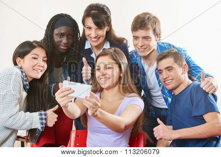 Successful teenagers take a selfie with their teacher at school