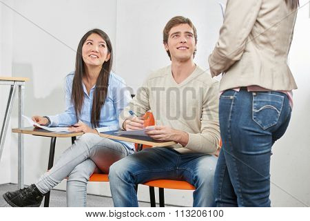 Teenage girl and boy taking a test in their high school classroom