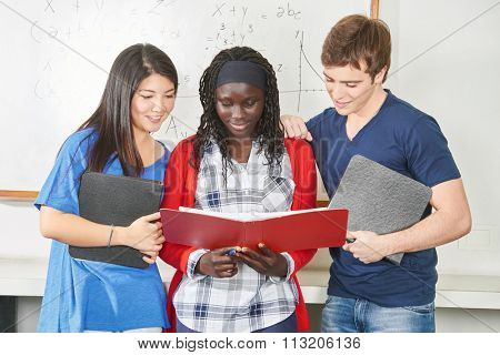 Three teenage students study together in school in their classroom