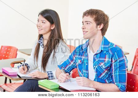 Smiling students taking notes in class in high school