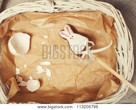 celebration for easter card, candy toy bunny with crashed egg on paper in basket vintage brown
