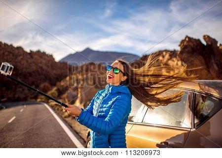 Woman making selfie portrait near the car