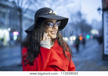 Smiling Lady in Red Coat and black hat and glasses, hold smartphone, Woman in red coat with smartphone in hands going through the city and looking shop windows. Urban Space, noise on image