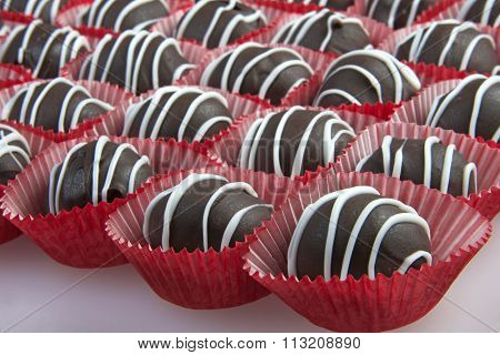 Chocolate Cake Balls with white candy melt accent stripping