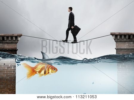 Concept of fake threat when businessman walking on rope above water with shark appear to be goldfish