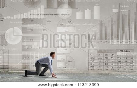 Young determined businessman standing in start position ready to compete