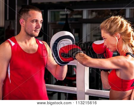 Female boxer  throwing  right cross at mitts