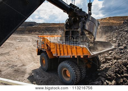 Loading big yellow mining truck.