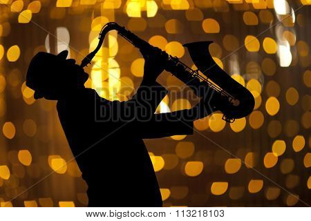 Saxophonist. Man playing on saxophone against the background of beautiful light