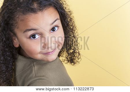 Studio shot of a beautiful young mixed race girl smiling and looking back over her shoulder