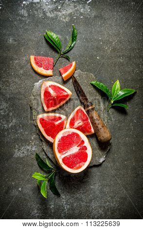 Fresh Grapefruit With Leaves And Knife On A Stone Stand.
