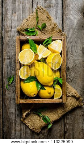 Lemons With Leaves In A Box On The Fabric. On Wooden Background.