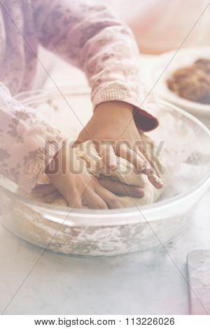 little girl kneads dough