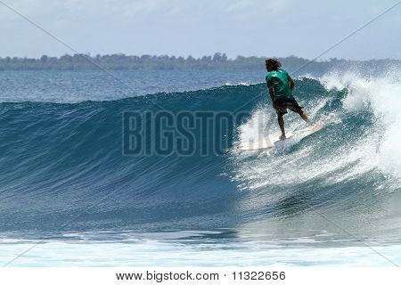 Surfer Riding Fast On Tropical Blue Wave