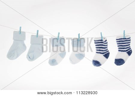 Blue And White Baby Socks On Clothesline, Isolated