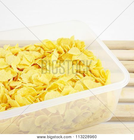 The tasty golden corn flakes in plastic container box