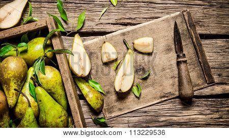 Sliced Pear With Knife And Leaves With A Box Full Of Pears.
