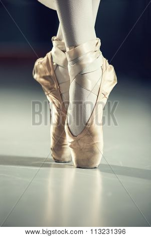 Dancer in ballet shoes, isolated on gray
