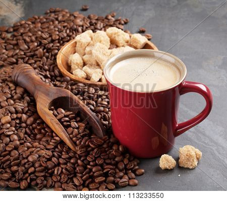 Coffee cup, beans and brown sugar on stone table