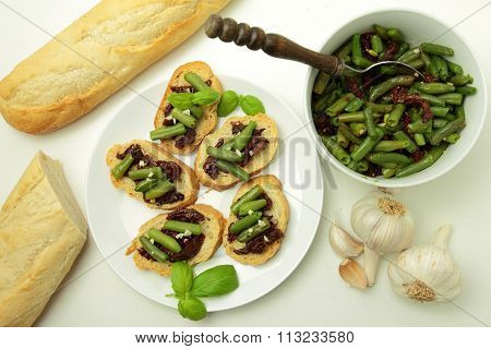 Angle view on bruschettas with sundried tomatos and green bean with garlic and basil for vegetarians