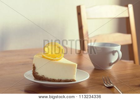 Lemon cheesecake and cup of coffee. Breakfast in cafe