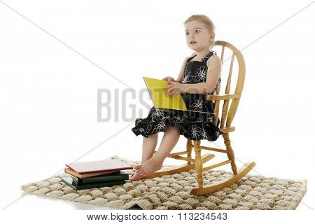 An adorable preschooler looking up from her rocking chair with an opened book on her lap.  On a white background.