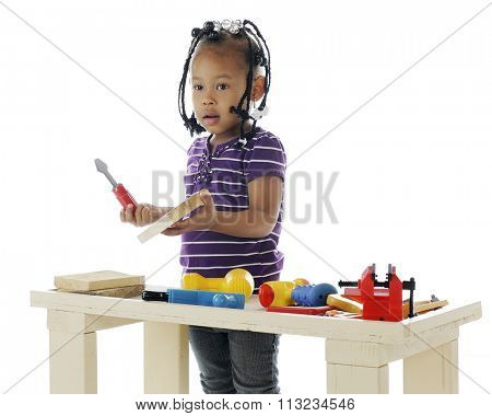 An adorable preschooler playing with the toy tools on a  workbench.  Taken on a white background.