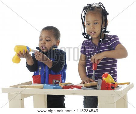A toddler brother and preschool sister playing together with the toy tools on a workbench.  Taken on a white background.