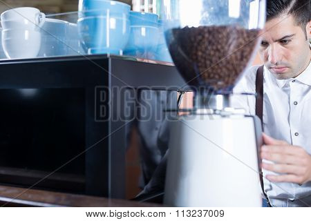 Bartender Grinds Coffee Beans