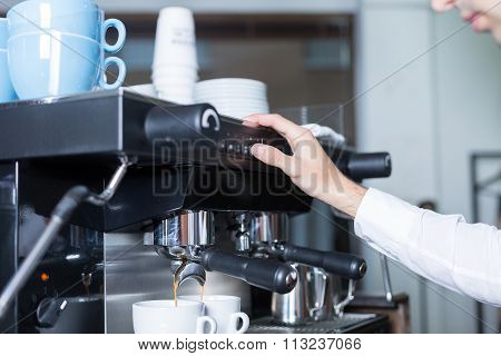 Bartender Pushing The Button On Coffee Machine