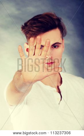 Young handsome man showing stop sign.