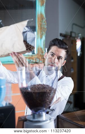Close-up Of Bartender Filling Up  Machine With Coffee Beans