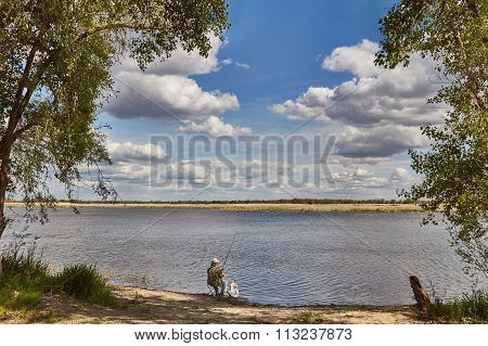 Clouds over the river and the fisherman with a rod