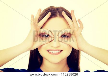 Young woman showing perfect sign on eyes.