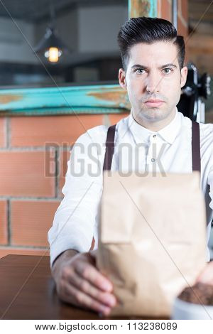 Portrait Of Bartender Looking At Camera While Holding Paper Bag