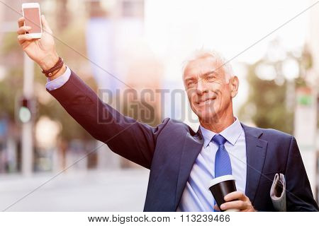 Businessman in suit catching taxi in city with cup of coffee in his hands