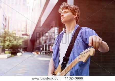 Portrait of young musician with guitar in city