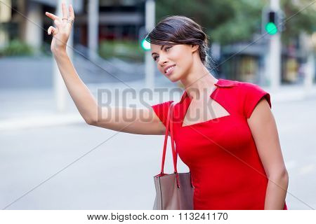 Businesswoman trying to catch a taxi in business city district