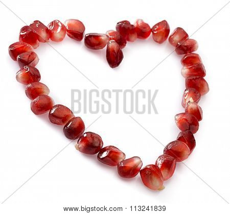 Heart symbol made from pomegranate seeds isolated on white background.